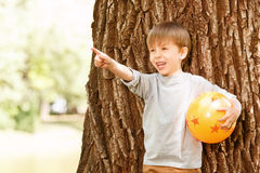 Boy under tree with rubber ball pointing upwards Royalty Free Stock Image