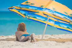 Boy under umbrella on a beach 1 Stock Photography