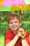 Boy under an umbrella during a rain Stock Photo