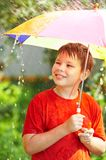 Boy under an umbrella during a rain Royalty Free Stock Photos