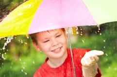 Boy under an umbrella during a rain Stock Photos