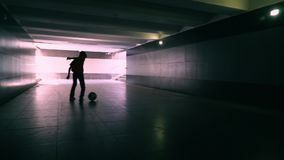 The boy in the underground passage plays with a soccerball stock video
