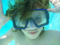 Boy underwater with mask. Boy underwater wearing mask and making a face stock photography