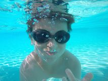 Boy underwater. Shot taken under water of 12 year old boy swimming in pool having fun, while on holidays at Tropical North Queensland, Australia Royalty Free Stock Photos