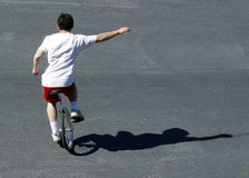 Boy on a unicycle. Boy riding on a unicycle royalty free stock image