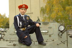 Boy in uniform with an armored troop carrier. Young cadet standing near an armored troop carrier Royalty Free Stock Photo