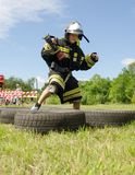 Boy in the uniform of fireman jumps on obstacles course of tires. Komsomolsk-on-Amur, Russia - August 8, 2016. Public open Railroader`s day. boy in the uniform royalty free stock photos