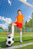 Boy in uniform with leg on football near woodwork Royalty Free Stock Image
