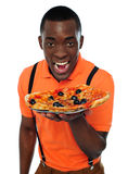 Boy in uniform offering pizza Royalty Free Stock Photo