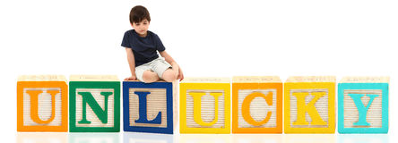 Boy Unlucky. Attractive sad seven year old french american boy sitting on unlucky over white background Stock Images