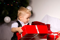 Boy unpack gifts under the Christmas tree Royalty Free Stock Photography