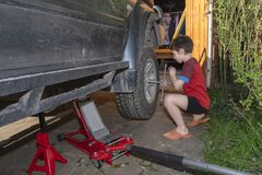 Free Boy Unscrews The Nuts On The Wheel Of Big Off-road Car. Wheel Replacement In The Yard Stock Photos - 182777433