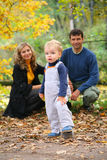 Boy with untied lace and parents in park Royalty Free Stock Photos