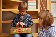 Boy unwrapping a Christmas present. Little boy unwrapping a Christmas present Stock Photo