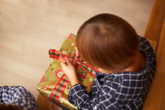 Boy unwrapping a Christmas present Royalty Free Stock Photos