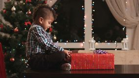 Boy unwrapping gift on table. Afro kid unwraps Christmas present. Eager to see what's inside. Cheerful toddler on Christmas eve stock video footage