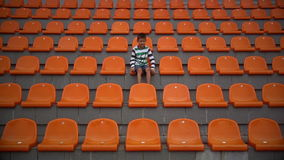 Boy upset at stadium team loses, fan Boy unhappy that his team conceded a goal on football. Boy looks at the stadium football match, a boy watching the game of stock footage