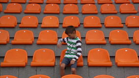 Boy upset at stadium team loses, fan Boy unhappy that his team conceded a goal on football. Boy looks at the stadium football match, a boy watching the game of stock video
