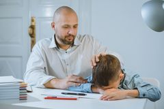 The boy is upset at a table, his father calms him. royalty free stock photo