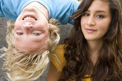 Boy (11-13) upside down by teenage girl (13-15), smiling, portrait royalty free stock images
