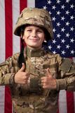 Boy USA soldier is showing thumbs up in front of American flag. Stock Photo
