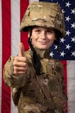 Boy USA soldier is showing thumbs up in front of American flag. Royalty Free Stock Photography