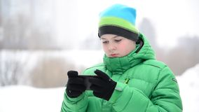 Boy uses a cell phone with gloves outside in winter stock footage