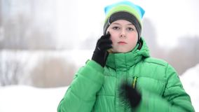 Boy uses a cell phone with gloves outside in winter stock video footage