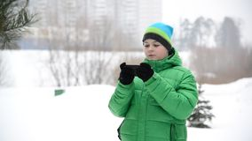 Boy uses a cell phone with gloves outside in winter. Boy uses a cell phone with gloves outside in a winter stock video