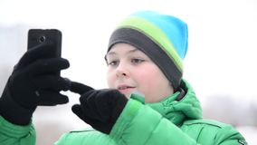 Boy uses cell phone with touchscreen gloves outside in winter stock video