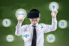 Boy uses VR headset and futuristic screen. Male elementary school student using virtual reality headset and futuristic screen Royalty Free Stock Images