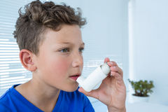 Boy using asthma pump. In clinic Stock Images