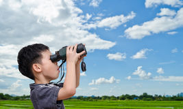 Boy using binoculars in field Royalty Free Stock Images
