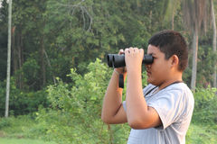 Boy using binoculars looking the nature. Thai boy looking the nature through binoculars Royalty Free Stock Image
