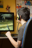 Boy using computer at home, playing game stock images