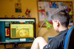 Boy using computer at home, playing game. Teenager using computer at home with headphones, play game in his child room Stock Photo