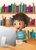 A boy using the computer inside the library Royalty Free Stock Images