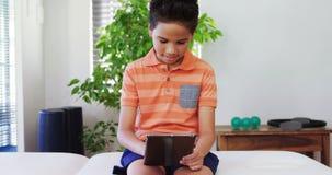 Boy using digital tablet on bed 4k. Boy using digital tablet on bed in hospital 4k stock video footage