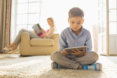 Boy using digital tablet on floor with mother reading magazine in background Stock Photography