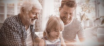 Boy using digital tablet with his father and grandfather in living room. At home stock photography