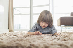 Boy using digital tablet while lying on rug in living room Stock Photography