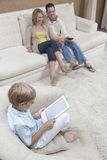Boy Using Digital Tablet With Parents Watching TV. Little boy using digital tablet with parents watching TV at home Royalty Free Stock Image