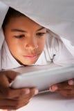 Boy Using Digital Tablet Under Duvet Stock Photos