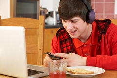 Boy Using Electronics Whilst Eating Breakfast Royalty Free Stock Photo