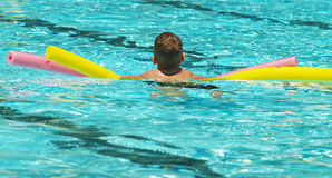 Boy using floats in pool stock images
