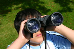 Boy Using His Binoculars. Focus on reflections in the object lenses Stock Photo