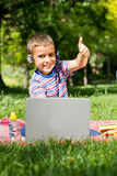 Boy using his laptop outdoor in park Stock Photography