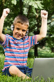 Boy using his laptop outdoor in park on grass Stock Photography