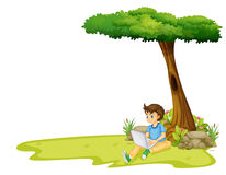 A boy using his laptop under a tree Stock Photos