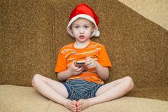Boy using his smartphone while seated in front of Royalty Free Stock Images